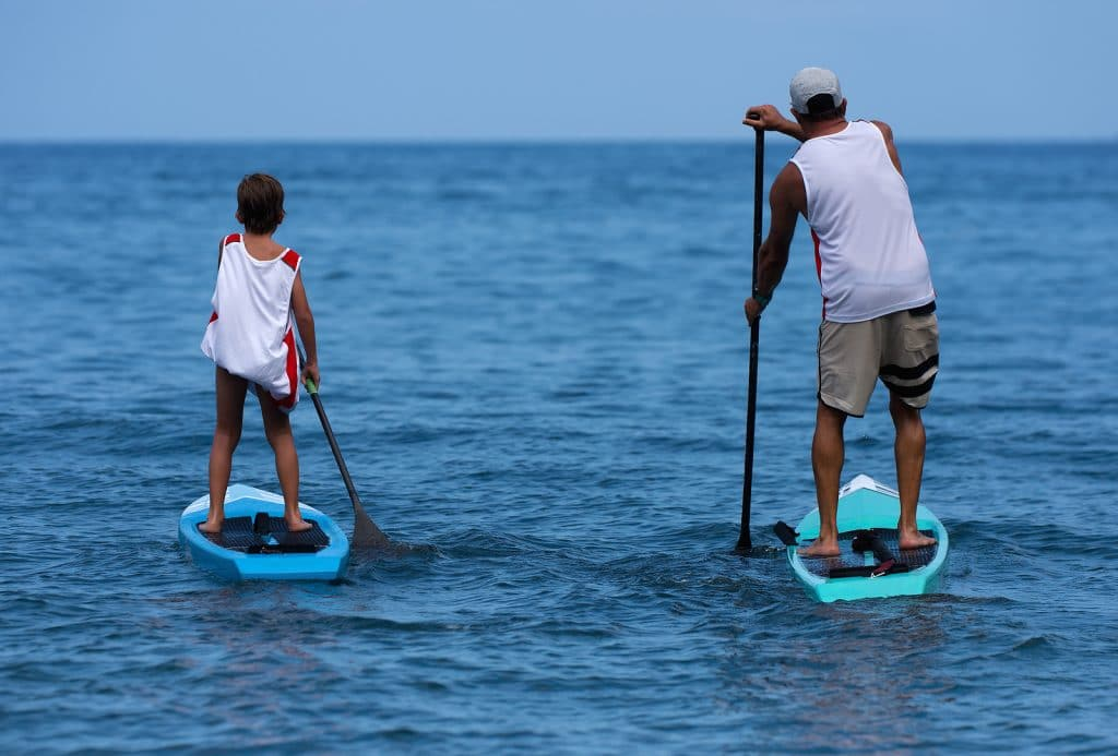 Little boy and young father, enjoying stand up paddle boarding in Cabo San lucas